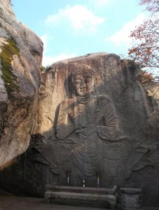 A giant rock has a carving of a Buddha sitting on a lotus, with a small platform underneath for candles. The carving is partially lit by sunlight, and above is a mostly clear blue sky