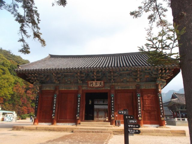 There is a rectangular wooden building, with red walls and detailed greenish painting under the roof, and a black tile roof - this is the entrance to the temple.