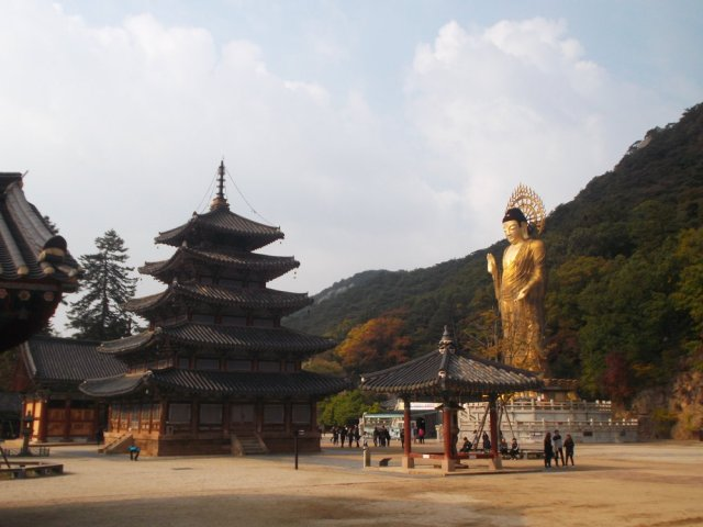 To the left is the five story traditional wooden Korean pagoda, and to the right is the tall golden statue of Buddha. Behind the giant Buddha is green hillside, and above is a partially cloudy sky. Below the Buddha we see tiny people, and thus realize just how tall the pagoda and the Buddha really are.